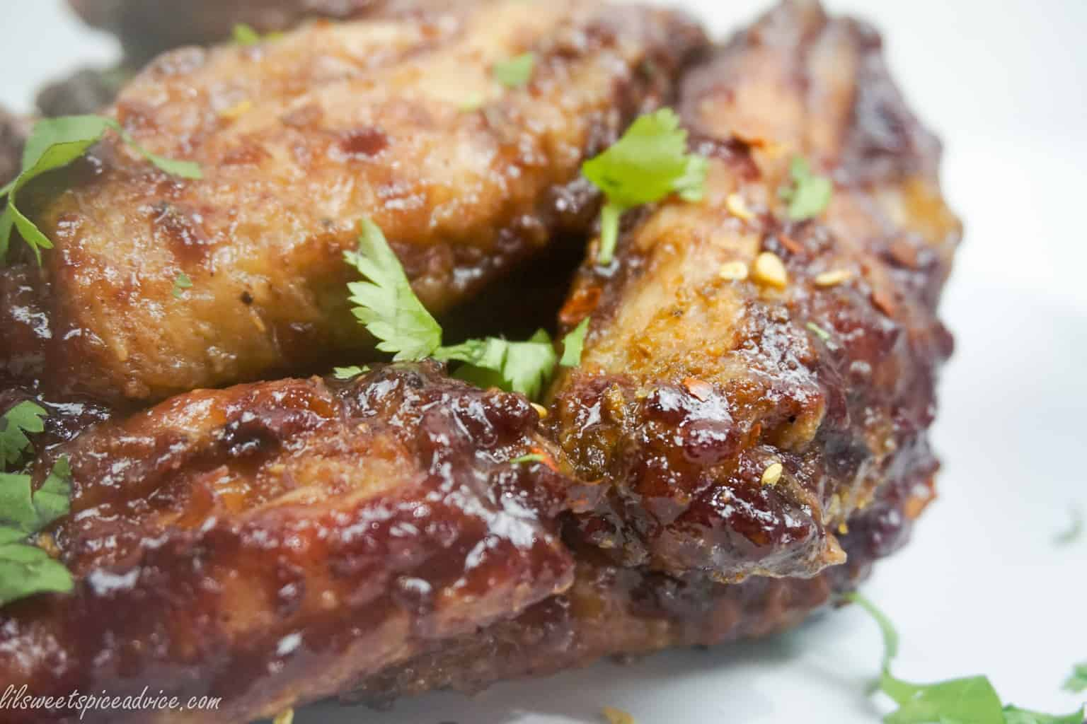 Spicy Cherry Glazed Chicken Wings--These Spicy Cherry Glazed Chicken Wings will make you forget all about BBQ sauce wings. Oven baked crispy chicken wings are tossed in homemade spiced cherry glaze and red pepper flakes.--lilsweetspiceadvice.com